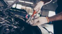Ein Mechaniker prüft den Ölstand bei einem Auto.
