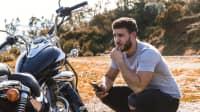 Mann kniet mit seinem Handy neben seinem Motorrad mit Panne