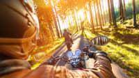 Man sitzt bei Sonnenaufgang auf dem Motorrad und fährt durch einen Wald