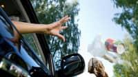 Frau wirft Kaffeebecher und Müll aus dem Fenster eines fahrenden Autos