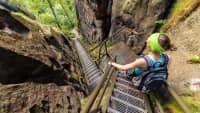 Frau geht eine steile Treppe in den Bergen hinunter