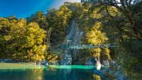 Eine Gruppe von Menschen geht über eine Hängebrücke zu den Blue Pools im Mount Aspiring National Park