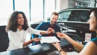 Ein Mann und eine Frau unterzeichnen einen Vertrag für ein Auto