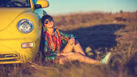 Frau macht Pause vom Autofahren und lehnt sich an ihr Auto