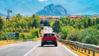 Rotes Auto fährt durch italienische Landschaft
