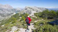 Älterer Mann wandert in felsiger Landschaft mit Blick zum Meer auf Mallorca