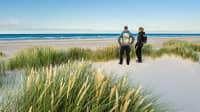Zwei Menschen stehen an einem Dünenstrand