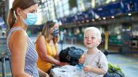 Mutter, Kind und Großmutter am Flughafen Check-in, das Kleinkind sitzt auf dem Gepäckwagen
