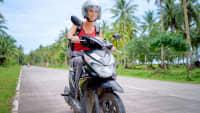 Eine junge Frau fährt mit einem Roller auf einer Straße in Thailand zwischen Palmen