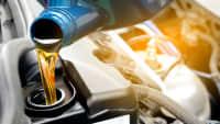 Öl lauft aus einem Kanister in einen Automotor
