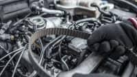 Mechaniker hält Zahnriemen in der Hand über dem Motor