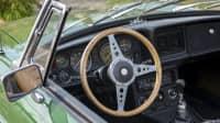 Blick in ein grünes Oldtimer Cabrio mit einem hölzernen Lenkrad