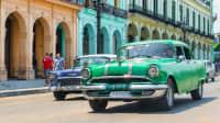 Ein grüner und ein blauer Oldtimer in einer Straße mit bunten Häusern in Havanna