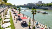Blick auf die sonnige Uferpromenade der Seine im Zentrum von Paris mit Sonnenschirmen und Spaziergängern