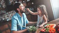 Kleines Mädchen füttert ihren Vater beim Mittagessen