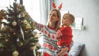 Frau schmückt mit ihrem Sohne den Weihnachtsbaum