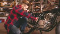 Mann schraubt an seinem Motorrad