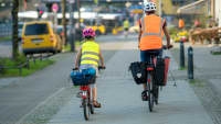 Elternteil fährt mit Kind auf dem Gehweg Fahrrad