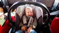 Kleinkind sitzt lachend im Kindersitz auf der Rücksitzbank eines Autos