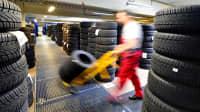 Ein Mitarbeiter eines Reifenhändlers fährt mit Sackkarre an aufgetürmten Reifen vorbei
