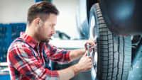 Ein Mechaniker montiert einen Reifen an ein Auto