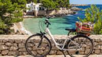 Ein weißes Fahrrad steht an einer Mauer auf Mallorca dahinter ein Strand