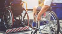 Rollstuhlfahrer wird auf Hebenbühne in den Bus gehoben