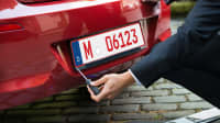 Autohändler schraubt ein rotes Nummernschild an einen Wagen