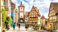 Touristen am Stadtturm in der mittelalterlichen Altstadt von Rothenburg ob der Tauber mit ihren bunten Fachwerkhäusern