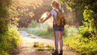 Frau auf Wanderweg im Wald, in der Abendsonne besprüht Ihre Arme mit Mückenschutz-Spray