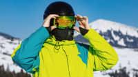 Skifahrer setzt seine Skibrille auf und trägst einen Mund-Nasen-Schutz