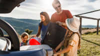 Familie lädt die Koffer aus ihrem Kofferraum