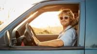 Mann mit Sonnenbrille fährt Auto