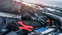 Mann mit Handschuhen schließt Starterkabel für eine Autobatterie an