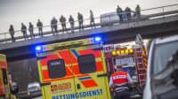 Menschen stehen auf eine Autobahnbrücke und schauen auf Unfall