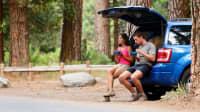 ein Paar macht Pause am Auto