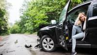 Junge Frau sitz mit Handy im  Auto nach einem Unfall