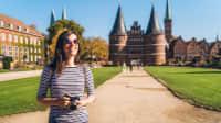 Frau mit Kamera steht vor dem Holstentor in Lübeck