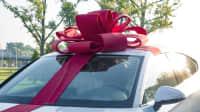 ein Auto mit einer großen Geschenkschleife auf dem Dach