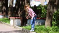 Junges Mädchen steht am Bordsteinrand