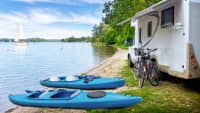 Ein Caravan mit Fahrrädern und Kajaks davor an einem See