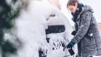Frau schließt eingeschneites Auto auf