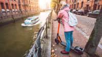 Eine junge Frau steht mit einem E-Scooter in Hamburg in der Speicherstadt an einer Brücke