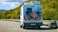 Campingbus mit Fahrrädern und Warntafel