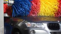 Bürste einer Waschanlage säubert die Kühlerhaube eines Autos