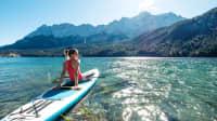 Frau sitzt auf ihrem SUP auf dem Eibsee
