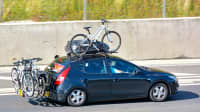 Ein überladenes schwarzes Auto mit Dachbox und 4 Fahrrädern auf der Autobahn