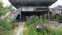 Ein Verlassener Bahnhof aus Beton mit Graffitis