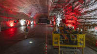 Eine riesiger rot angestrahlter Saal in einem Bergwerk