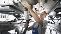Mechaniker rüstet einen Diesel Partikelfilter bei einem Auto nach
